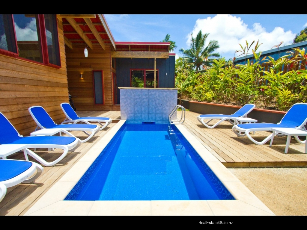 Private swimming pool and sunbathing deck amidst lush surroundings